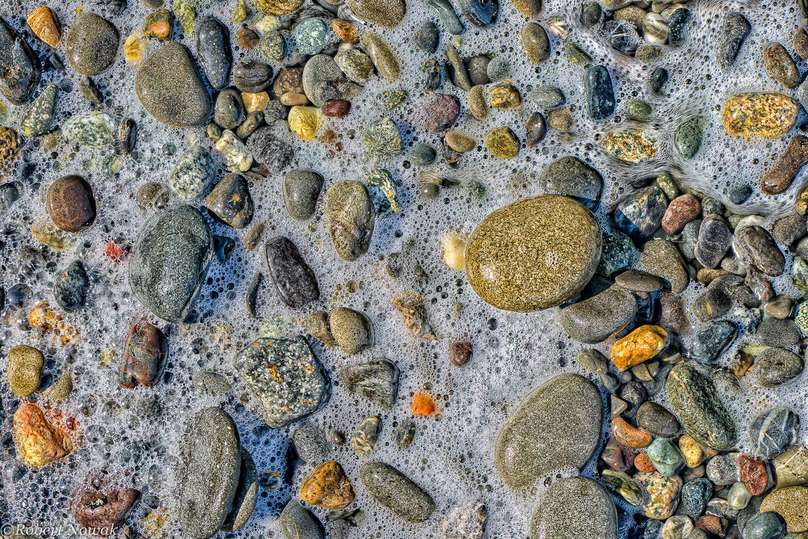 Bubbles left behind by receding waves mix with stones on the beach, Dungeness National Wildlife Refuge, Washington